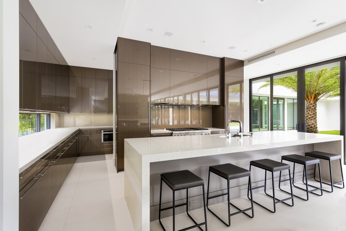 Dura Supreme kitchen design by Danny McMullen of Distinguished Kitchens and Baths. An ultra modern style kitchen with glossy cabinets and a waterfall countertop.