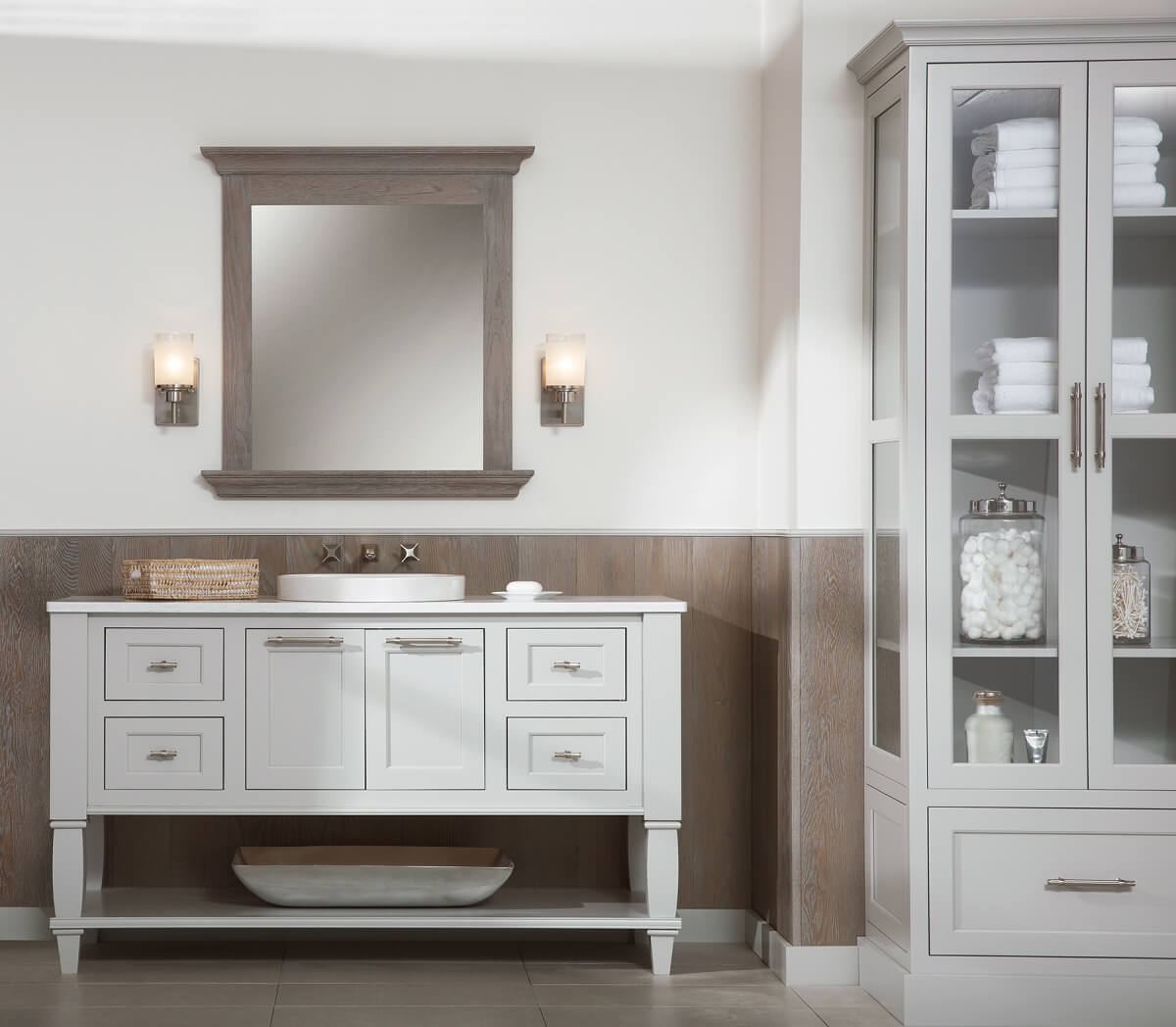 Transitional style bathroom featuring Dura Supreme Cabinetry's furniture vanity style five in the Kendall Panel (inset) door style with Sliver Mist paint finish. Mirror and paneling in a contrasting Weathered Finish