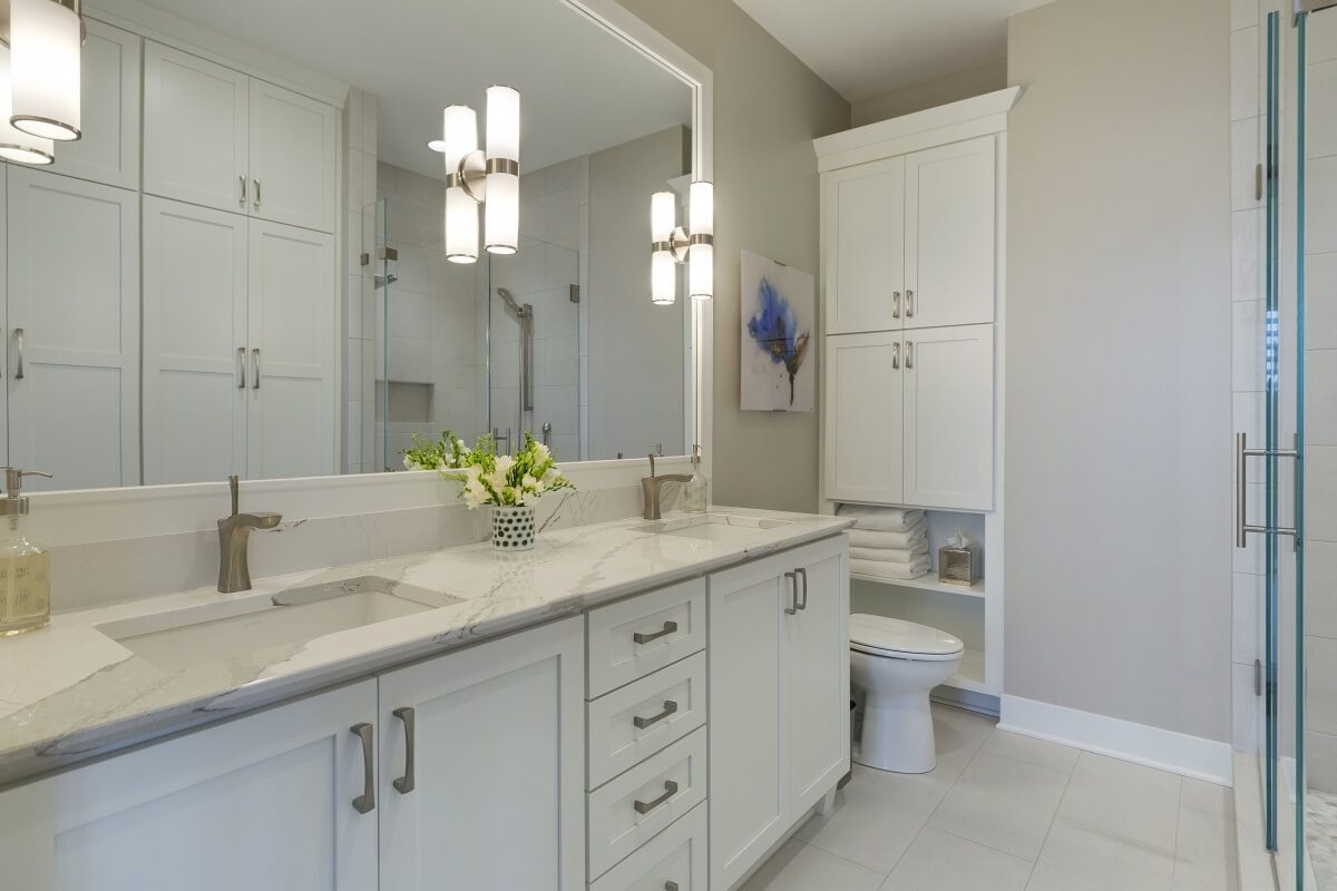 A Transitional style bathroom featuring white undermount sinks and Dura Supreme Cabinetry. Designed by Ispiri Design Build Remodel.