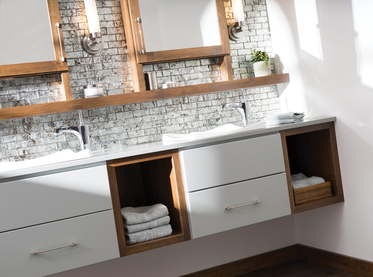 A beautiful bathroom featuring the mix of gray tones with wood accents. Dura Supreme Cabinetry floating vanity shown in Chorma door style with custom paint finish and Cherry Praline Finish.