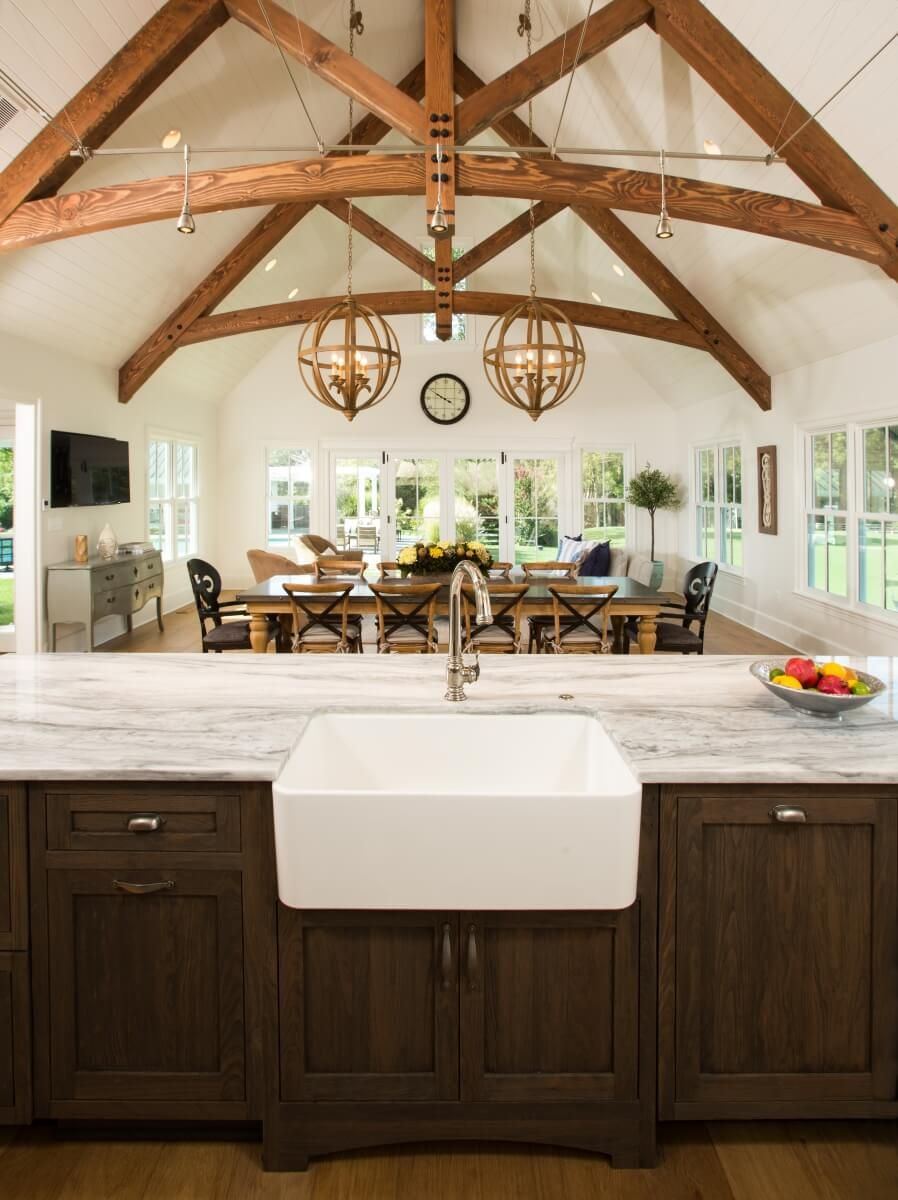 Commanding rustic beams and the farmhouse sink are so appropriate for this space