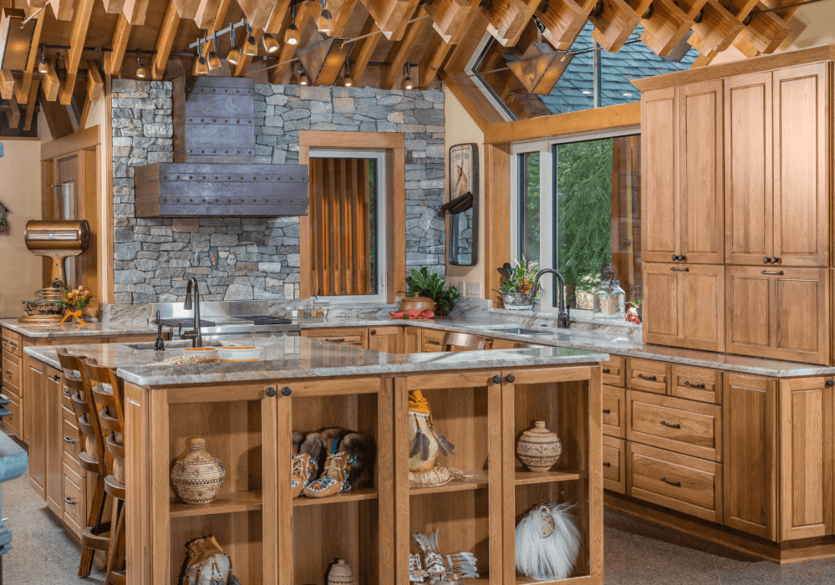 A stunning mountain lodge inspired kitchen, featuring a gorgeous hand-made copper range hood and Dura Supreme Cabinetry. Kitchen designed by Hollie M. Ruocco, CMKBD of Creative Kitchen Designs, Inc and photographed by DMD Photography. Door style: Chelsea in Hickory with Butternut finish.