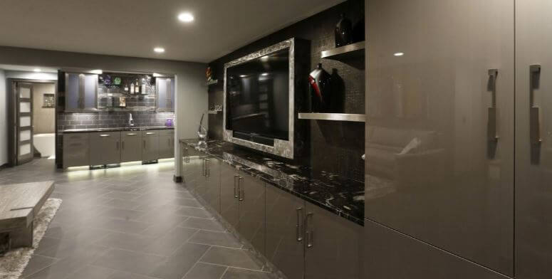 A modern and contemporary basment remodel with and entertainment room. Dura Supreme Cabinetry in the Talia-Vertical door style with the Wired Mercury wired gloss foil.