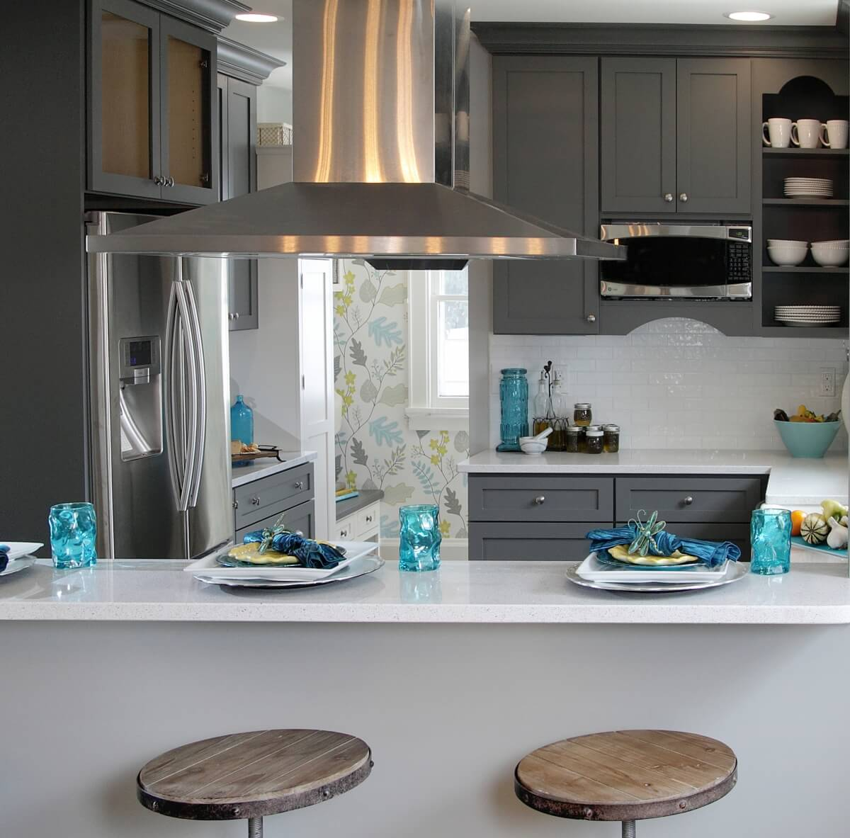A dark gray painted kitchen with bold blue accents and brightly colored wallpaper.
