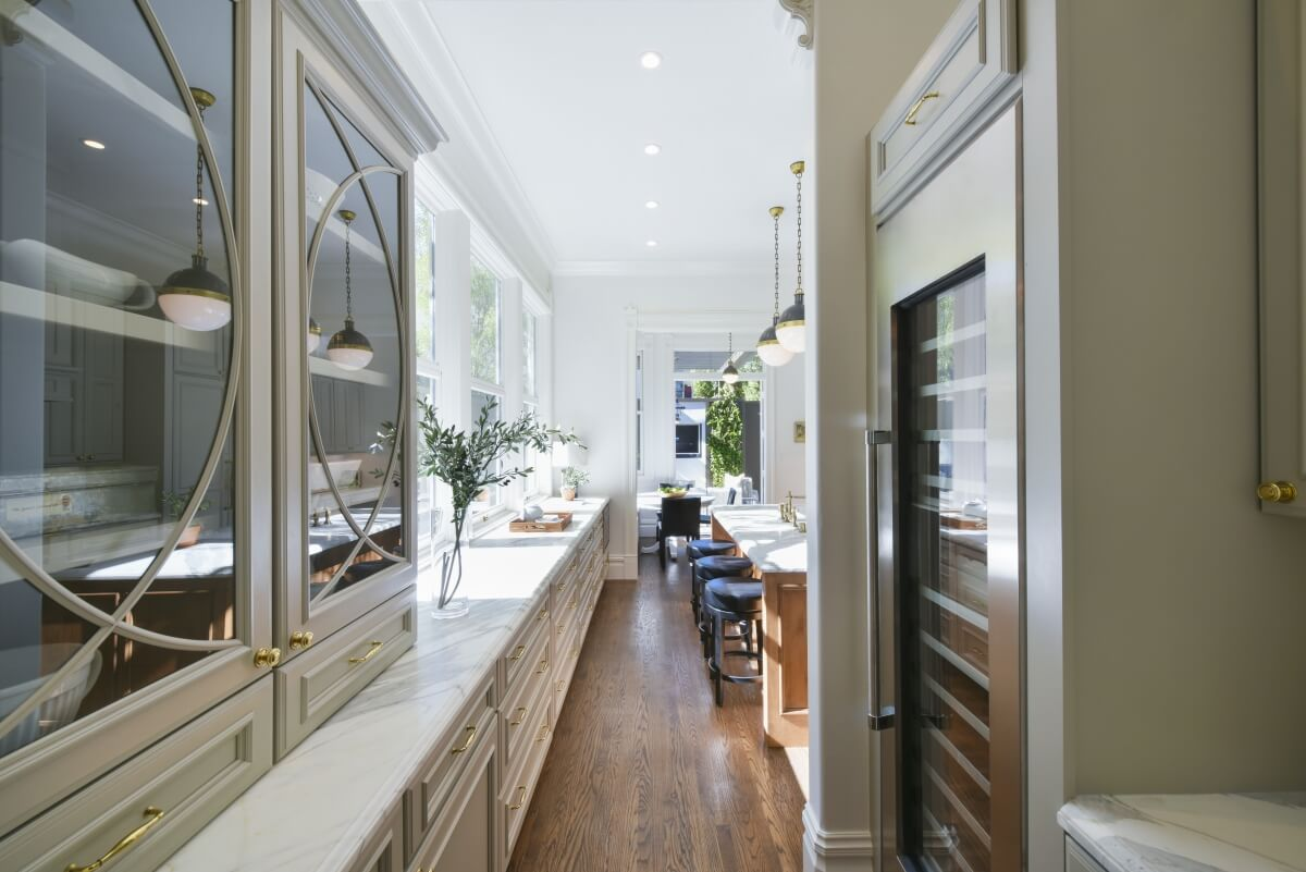 An elegant kitchen with glass mullion cabinet doors and a gray cabinets.