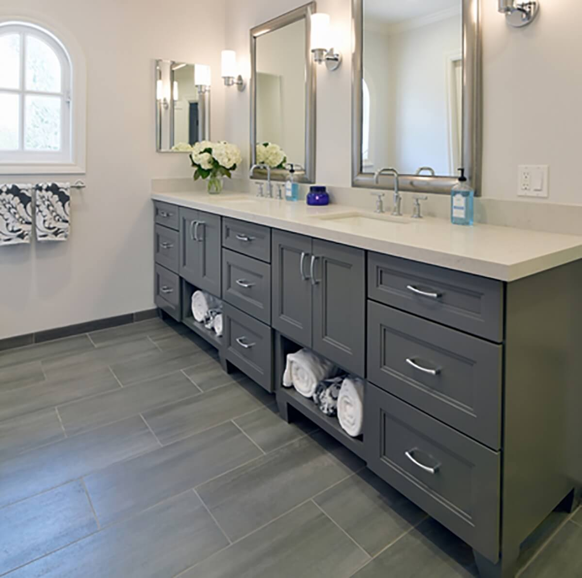A master bathroom with a dark gray painted vanity with open storage for bath towels. Featuring a nickel finish on the cabinet hardware, plumbing fixtures, faucet, light fixtures, and bathroom mirrors frames. A lighter gray colored floor tile complements the dark gray vanity cabinets.