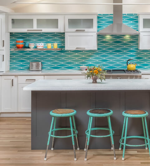 A bright and vibrant kitchen design with a dark gray kitchen island that creates contrast tothe white cabinets and bright blue backspalsh.