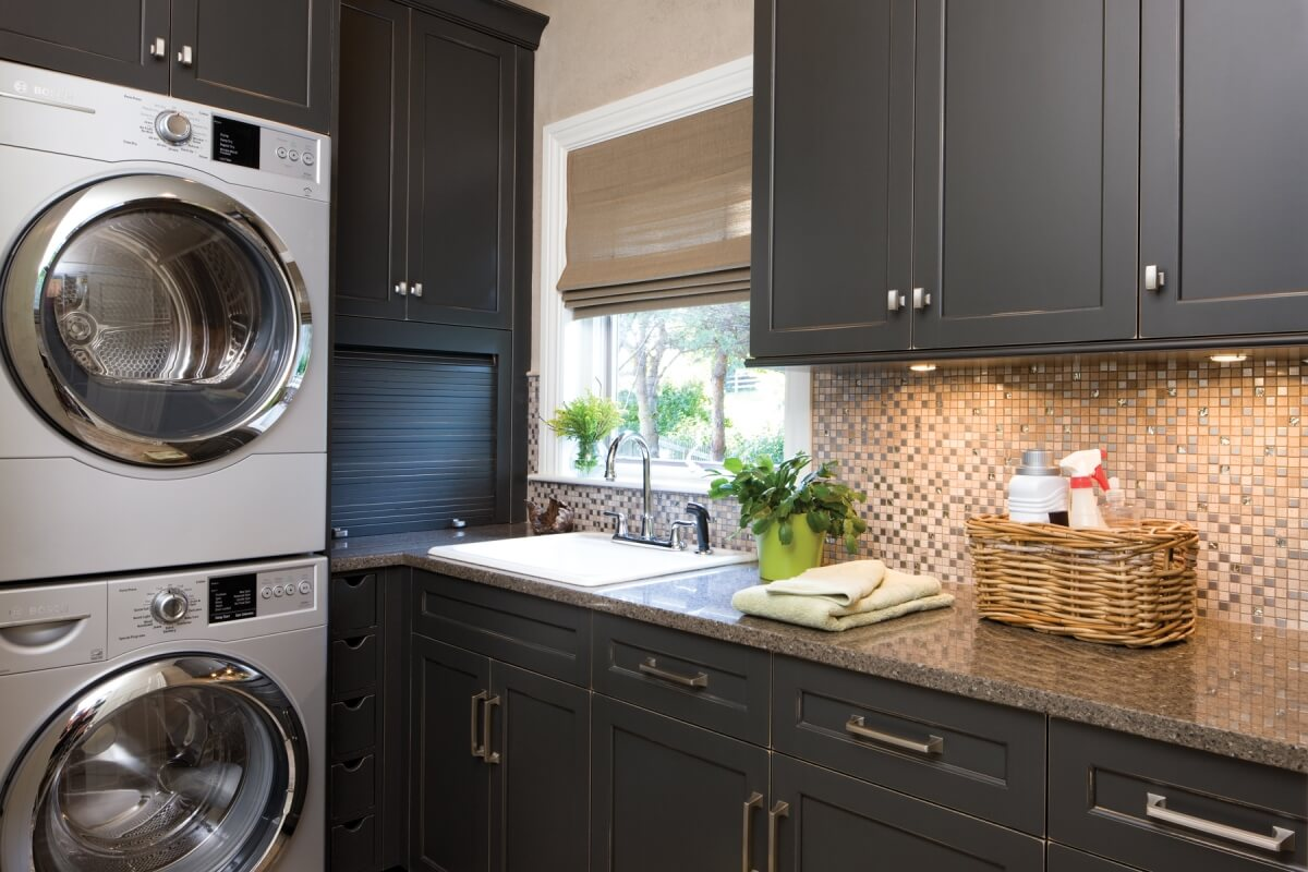 A laundry room remodel with almost black, dark gray painted cabinets from Dura Supreme Cabinetry with stainless steel appliances.