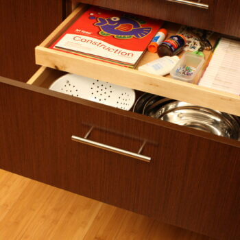 Shallow Roll-Out Above Drawer used for Kids Homework Supplies. Kitchen cabinet storage solutions by Dura Supreme Cabinetry.
