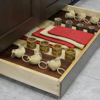 Miscellaneous items can find a home in a Dura Supreme Toe-Kick drawer hidden at the foot of your cabinets. It is the perfect place for stashing your seasonal table dressings, linens, candles, and more!
