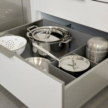 Modern kitchen cabinets featuring Deep Drawer Organizer for Stainless Steel Drawers With Pots and Pans by Dura Supreme Cabinetry.