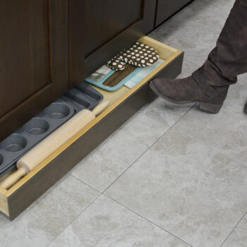 Miscellaneous items can find a home in a Dura Supreme Toe-Kick Drawer hidden at the foot of your cabinets. This convenient solution adds additional storage to your home. It's great for bakeware, spare oven mitts, rolling pins, cutting boards, and so much more!