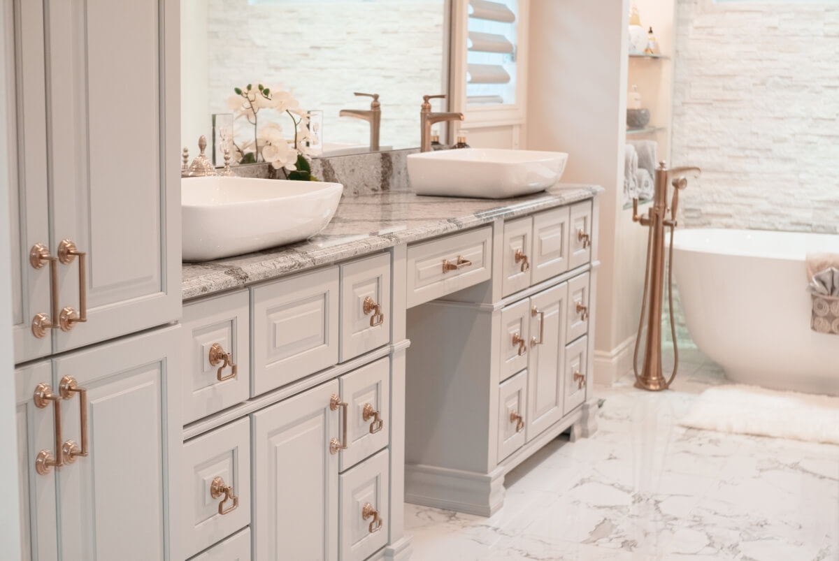 A warm and inviting master bathroom with warm brass hardware and a gray color palette. Showing a close up of the vanity cabinet doors.