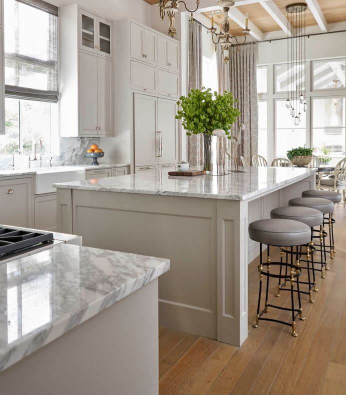 A warm gray painted kitchen design with a large kitchen island with seating for four.