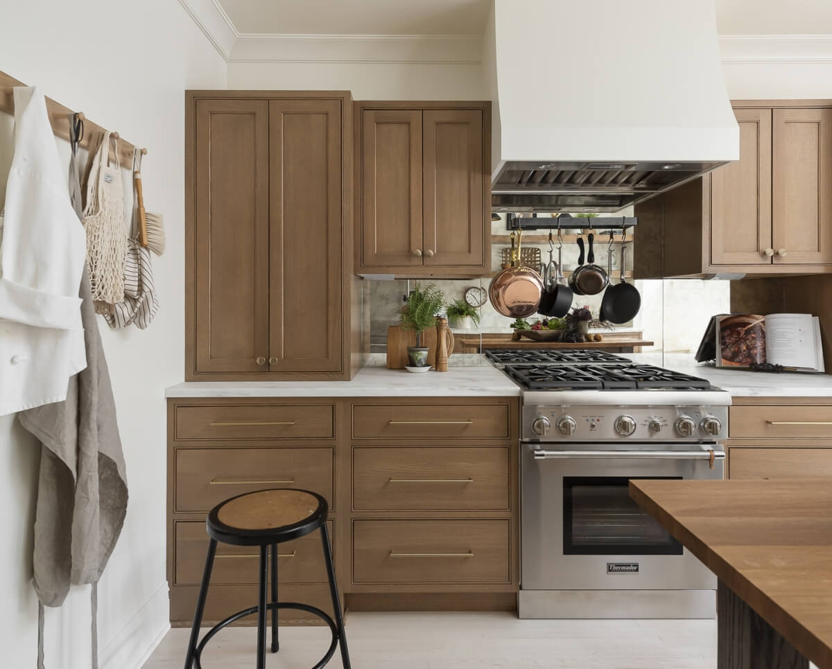 A straight on view of the kitchen remodel with light stained wood cabinets, white countertops, white painted wood hood, and dramatic mirror backsplash.