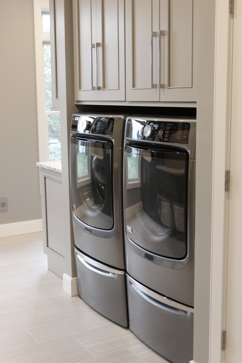A warm gray painted laundry room with gray painted cabinets.