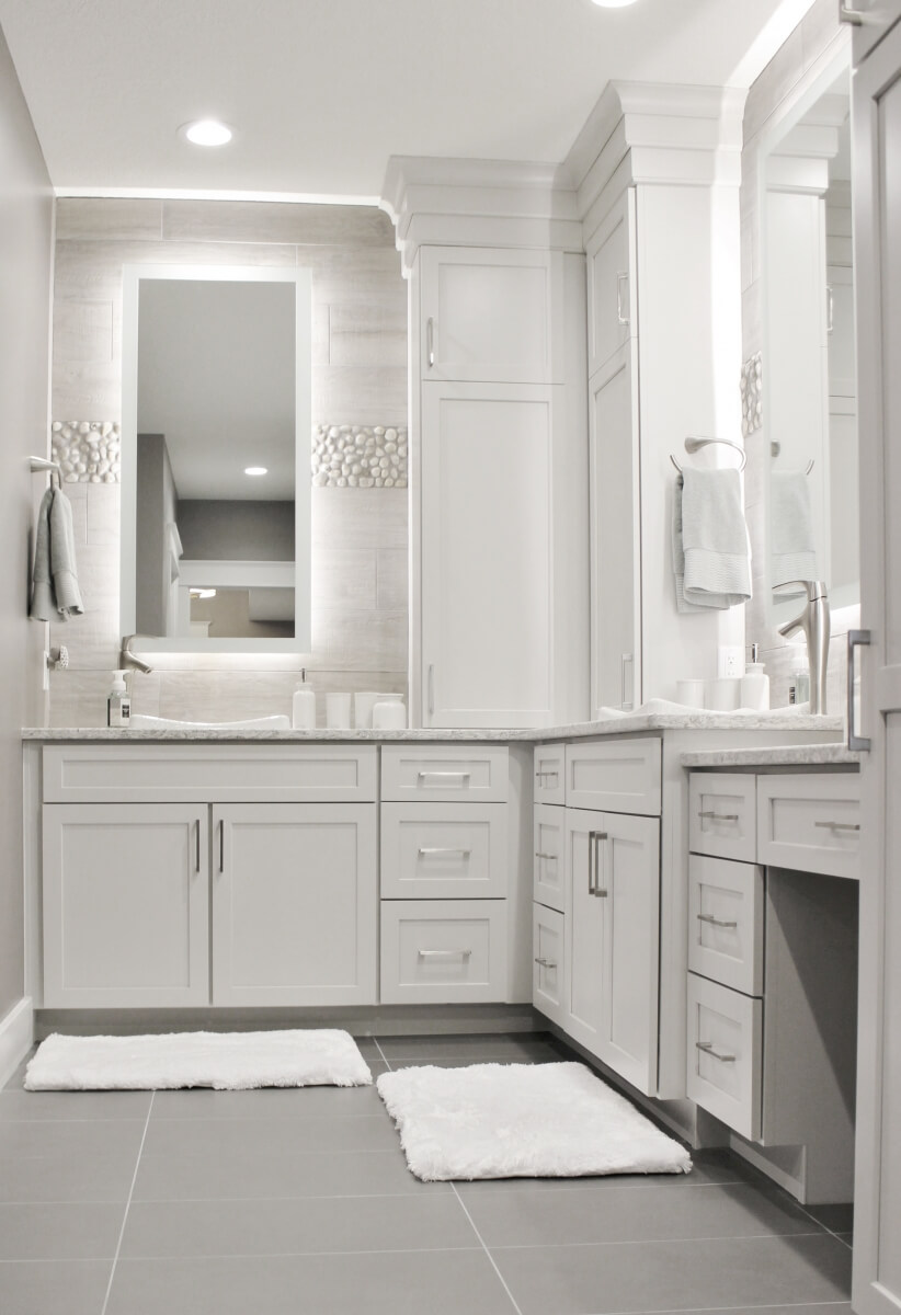 A stunning bright white master bathroom with a light white-gray painted vanity.