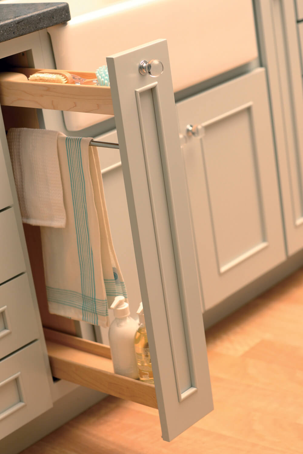A Pull-Out Towel Bar cabinet by Dura Supreme provides a dedicated space for storing towels, sponges, soaps, and hand-sanitizers next near the sink area.
